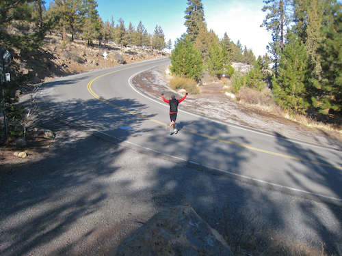 Trail runner bravely and victoriously crossing Archie Briggs Road along the Deschutes River Trail